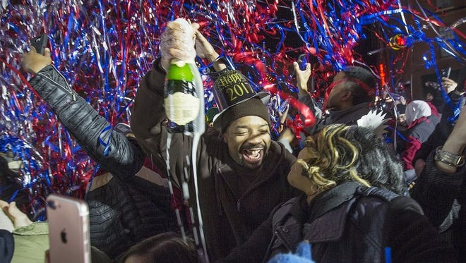 Ronald Gill and Kellie Perkins, of Indianapolis, celebrate with champagne as the clock strikes midnight during New Year's Eve on Georgia Street, downtown Indianapolis, Saturday, Dec. 31, 2016.