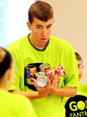 Clayton Oney, 15, of Union, a volunteer at GO Pantry, carries an armload of canned goods to fill a box with food which will be delivered to a school for distribution to kids in need. The group was working at Grace Episcopal Church, Florence.