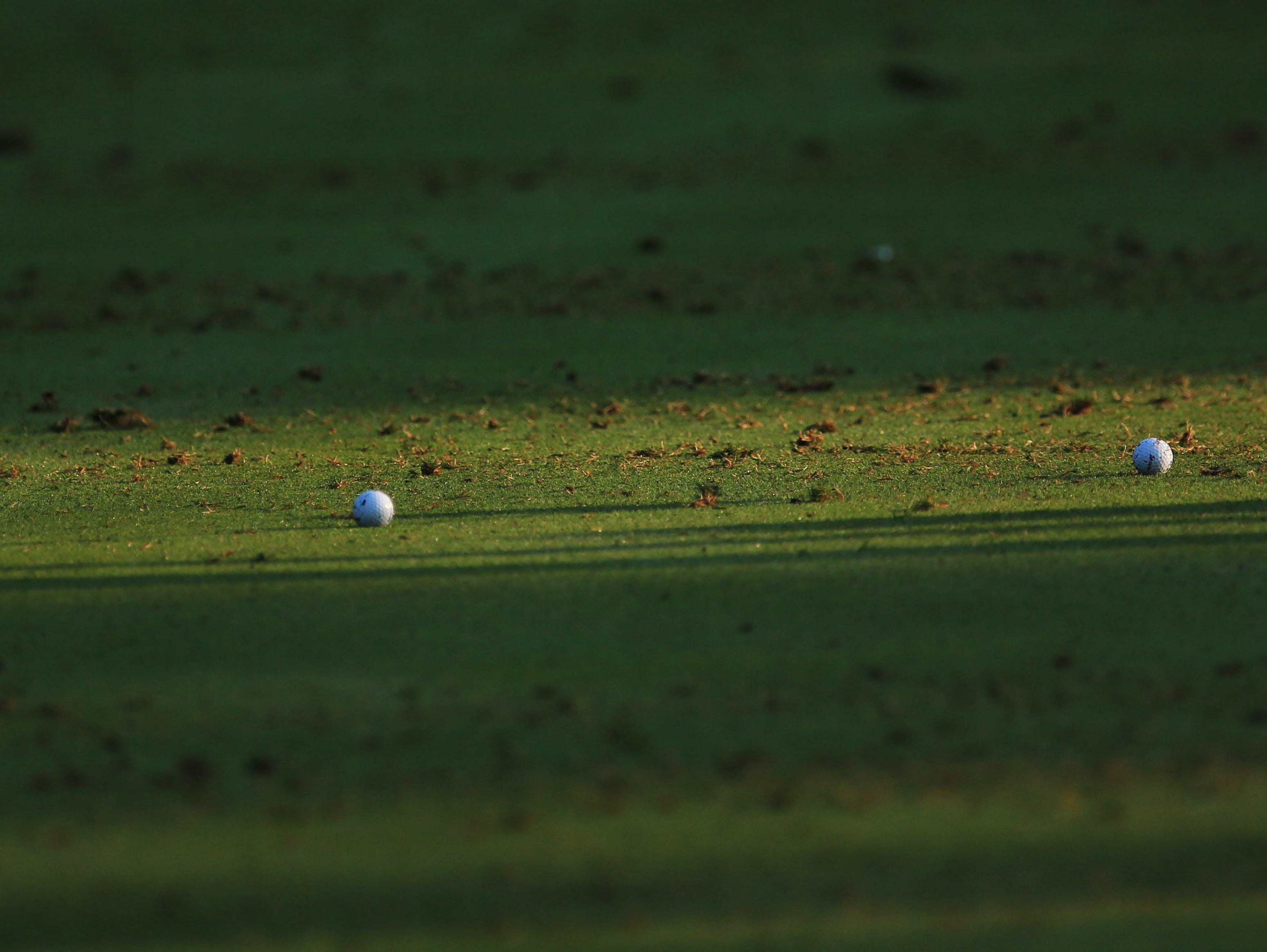 Two lonely golf balls sit on the practice range at Oak Hill Country Club.