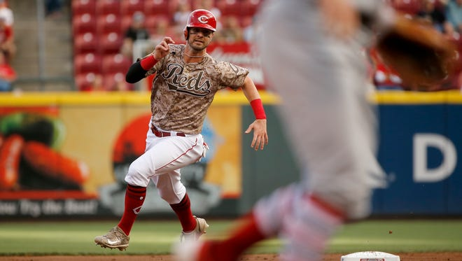 Cincinnati Reds left fielder Jesse Winker (33) rounds second on his way to scoring on a Joey Votto RBI double in the bottom of the first inning of the MLB National League game between the Cincinnati Reds and the St. Louis Cardinals at Great American Ball Park in downtown Cincinnati on Friday, Aug. 4, 2017.