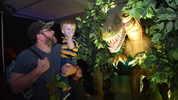 """John Long and his sons Braxson Wolf, 18 months, and Jameson Long, 8, play with an animatronic dinosaur which is part of the """"Discover The Dinosaurs"""" exhibit at the Alexandria Riverfront Center. The exhibit continues from 10 a.m. to 7 p.m. Sunday."""