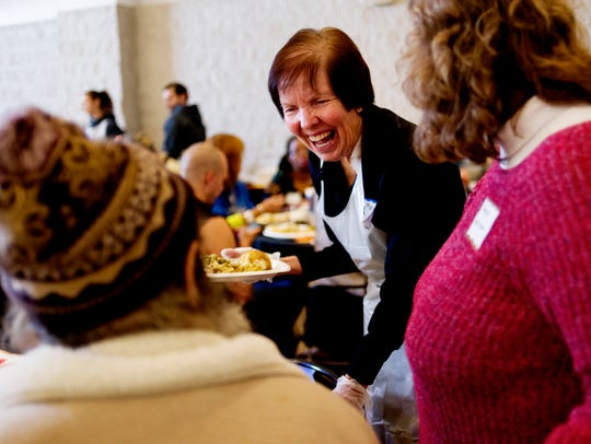 Volunteer Mary Langdon serves up a meal during the