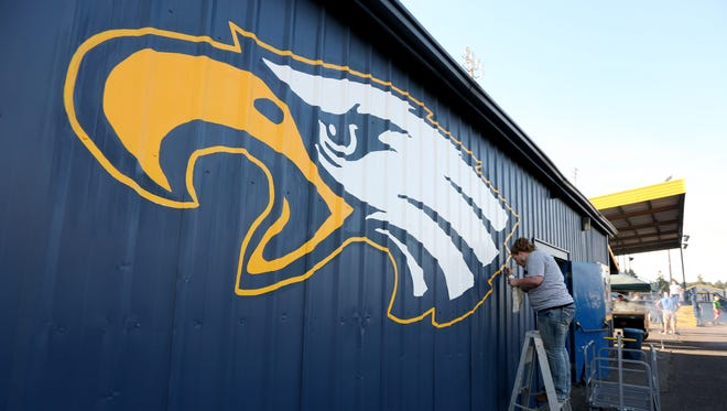 Kiersten King touches up an Eagle logo in the stadium during a ceremony to dedicate Stayton High School's new turf field on Wednesday, Sept. 14, 2016.