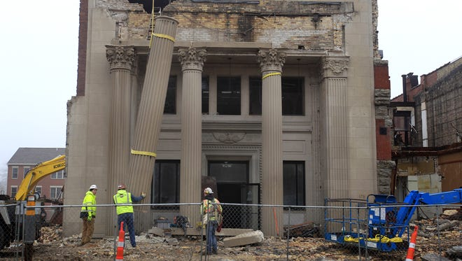 Miron Construction Co. employees remove the limestone pillars from the  former First National Bank on Main Street in Menasha in December 2014.