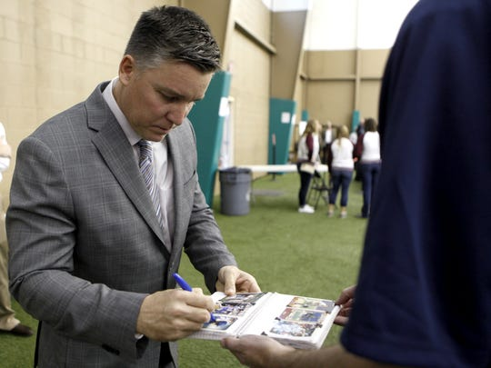 Bill Mueller signs an autograph for a fan before speaking