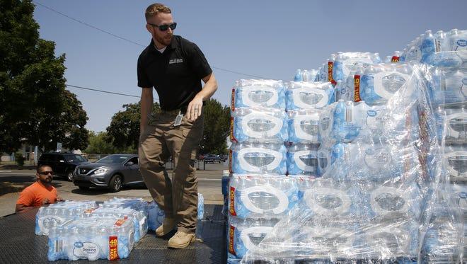 Salem Emergency Manager Greg Walsh stacks water bottles at a water distribution site at the Oregon State Fairgrounds in Salem, Oregon, on Wednesday, June 6, 2018.