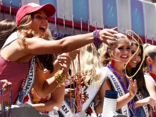 Miss Teen Montana Elley Munson throws beads during the Miss USA and Miss Teen USA Mardi Gras parade Monday afternoon in downtown Shreveport.