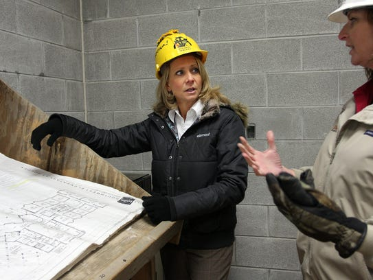 Principal Chris Parker, left, talks with project manager Rebecca Welsh as they look over plans at the new southwest elementary school. Harrison Elementary was opened in 2009.