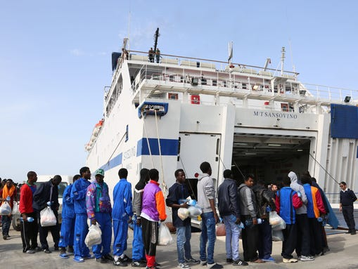 Migrants board a ferry as they leave the Island of