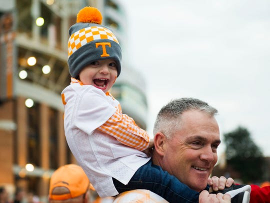 Mike Reel holds 2-year-old Ben Reel before a game between