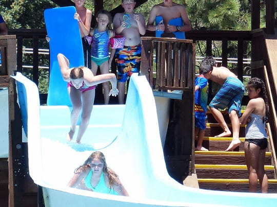 A swimmer takes a flying leap on the flume at Ruidoso's municipal pool.