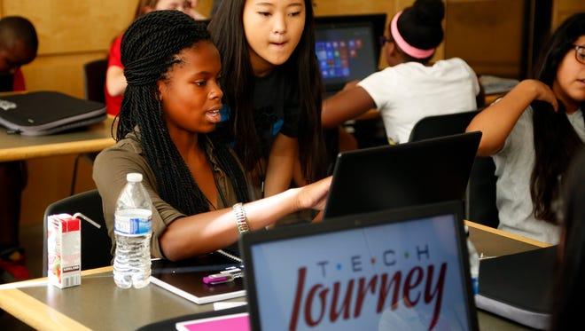 Ester Ubadigbo, 13, sets up her laptop with help from Kate Plagge at Tech Journey, a local organization to help kids connect and train with technology at Central Academy Tuesday, July 14, 2015.