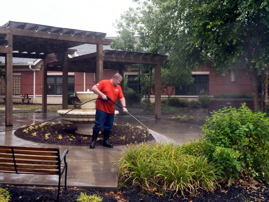 Jay Bisping, Home Depots district manager for Virginia and East Tennessee, pressure washes a patio at the Ben Atchley Tennessee State Veterans' Home Thursday, June 21, 2018. Bisping and a team of volunteers from Home Depot are helping clean up the grounds around the home and have even installed a paver patio.