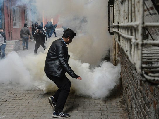 People react as tear gas is sprayed during clashes