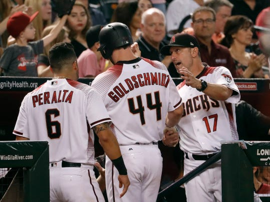 Arizona Diamondbacks' Paul Goldschmidt (44) is greeted in the dugout by manager Torey Lovullo (17) and David Peralta (6) after scoring on a double by J.D. Martinez during the third inning of a baseball game against the Colorado Rockies, Wednesday, Sept. 13, 2017, in Phoenix. (AP Photo/Matt York)