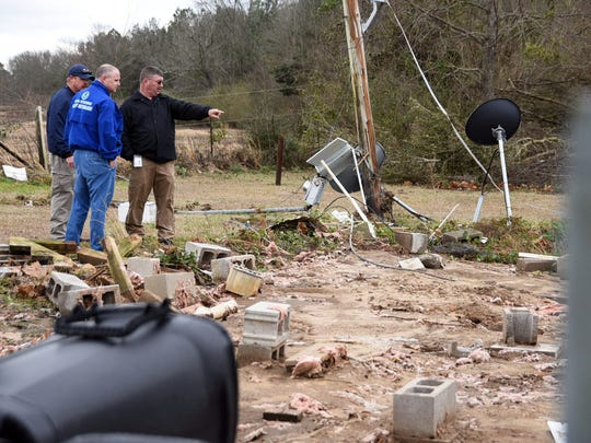 National Weather Service and emergency management officials look at debris from a tornado that hit Lamar County on Feb. 23.