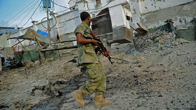 A solder walks past at the scene of a car bomb attack and armed raid by Al Shebab militants on the Maka al Mukarama Hotel in Mogadishu on March 27, 2015.