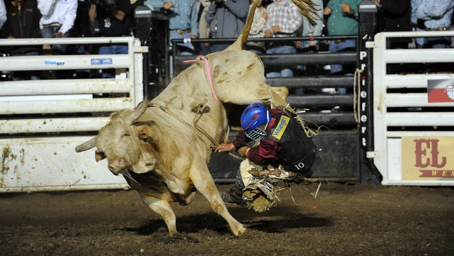 Mike Lee from decatur, TX is tossed by Wolf Deer at the 2014 Professional Bull Riders event at the Salinas Sports Complex.