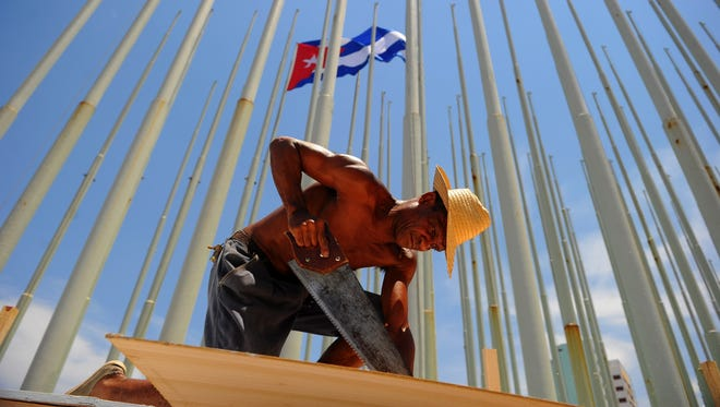 Workers set up a dais at the U.S. embassy on Havana's Malecon seafront, on Aug. 13, 2015.