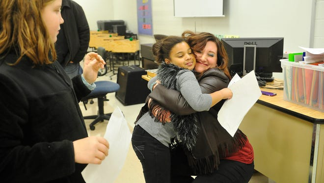 Songwriter Shantell Ogden hugs fifth-grader Abby Hayek as Courtney Gray, left, watches after Ogden performed a song inspired by Mt. Juliet's Random Acts of Kindness Challenge on Wednesday, Nov. 17, 2015, at Mt. Juliet Elementary School.