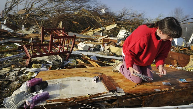 Diana Davis looks for family photos after a tornado tore through Wednesday, as she sifts through the rubble of her father-in-law's home in Lutts, Tenn., Thursday, Dec. 24.  At least 14 people were killed in as spring-like storms mixed with unseasonably warm weather and spawned rare Christmastime tornadoes in the U.S. South, officials said Thursday.