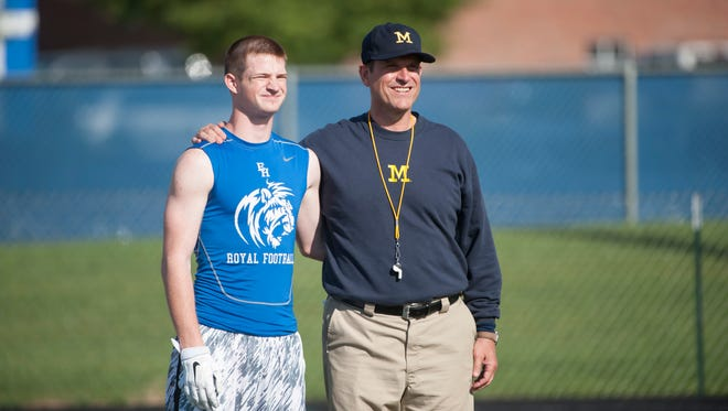 Jim Harbaugh poses for a photo with an attendee of a satellite camp at Bishop Chatard high school in Indianapolis.