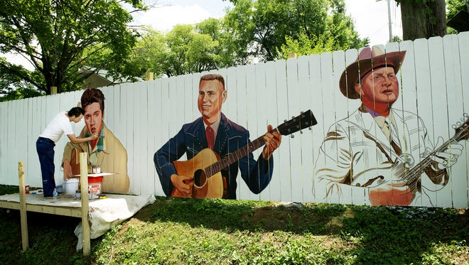 Artist Scott Guion paints music legends on a fence leading up to the House of Blues Studios on East Iris Drive June 25, 2014 in Berry Hill. Along with Elvis Presley, George Jones and Bill Munroe, Guion will be adding Dolly Parton, Jimi Hendrix, Flatt and Scruggs and others in coming days.