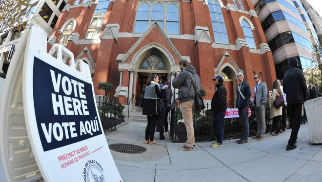 People crowd a side walk in downtown Washington, D.C. waiting to enter a church, turned polling station on Tuesday.