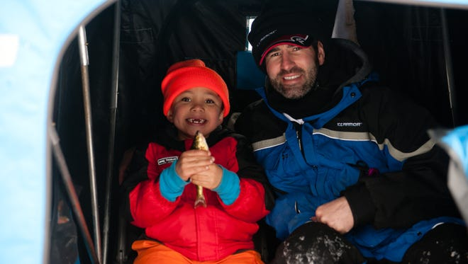 """Iowa fishing guide Kirk Moe and his boy are all smiles with a fresh caught yellow perch. The """"Hooked on Hardwater"""" program at The Rapid City Club for Boys gives many underprivileged boys the chance to go ice fishing for their first time and make a connection with a positive role model."""
