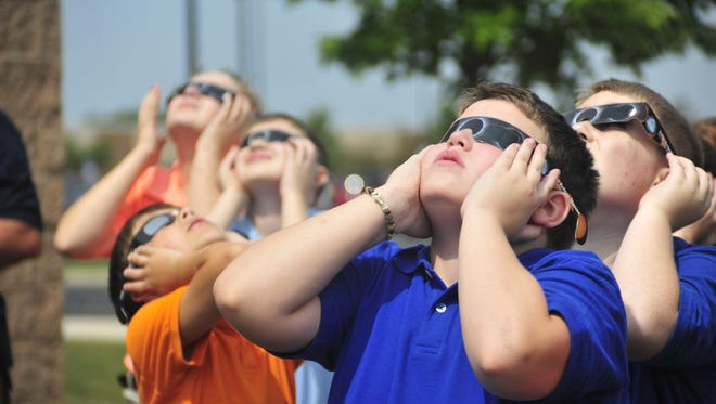 Sam Gregg and several of his fifth-grade classmates at Galion Intermediate School use special glasses to look at the solar eclipse Monday.