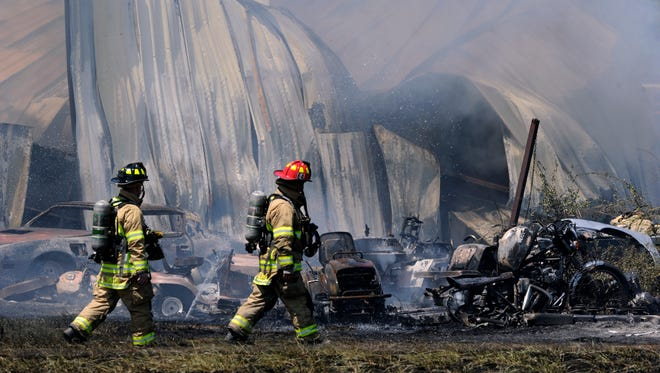 Abilene firefighters walk past the remains of a garage workshop Wednesday Aug. 30, 2017, near Hamby along State Highway 351. The building and vehicles surrounding it caught fire, along with the brush. Smoke could be seen from businesses near Interstate 20, one of which called the fire in shortly after 12:30 p.m.
