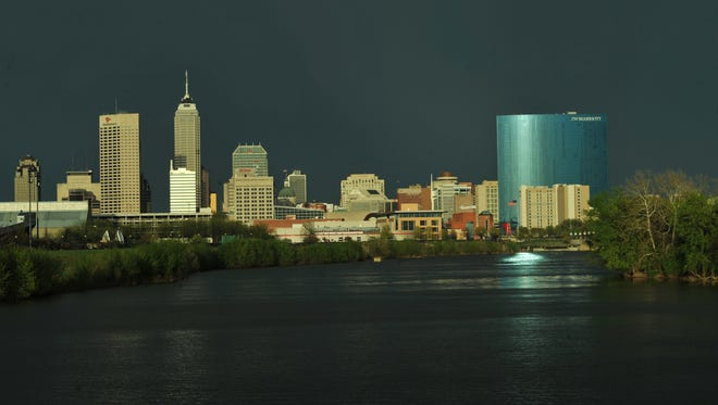 The low sun reflects off the downtown Indianapolis skyline looking down the White River from New York Street, after a storm blew over and the sun emerged from behind the clouds, Tuesday April 29, 2014. One Americatower, Chase Tower, JW Marriott
