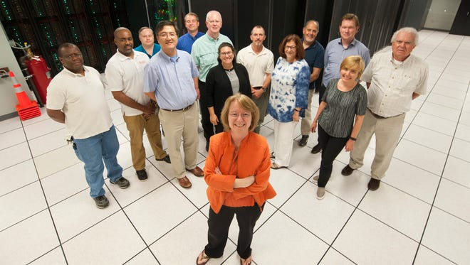 Clemson Professor Amy Apon, center, chairwoman of the Computer Science Division, stands with her team in front of the Palmetto Cluster supercomputer at the Information Technology Center in Pendleton.