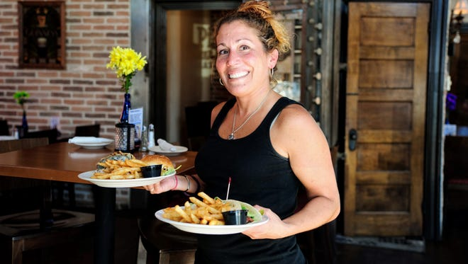 Candace Fiorentino brings lunch to a couple at the bar. The Pint Pub and Eatery in Millsboro has not seen the customary seasonal fall off that was common just a few years ago.