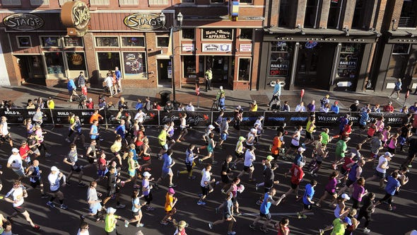 Runners pass by the honky-tonks of Lower Broadway as