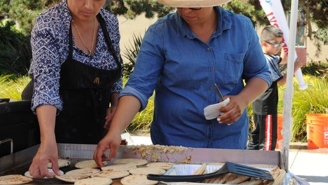 Cataria Osornio (left) and Sinthia Jimenez (right) prepare masa, Spanish for dough, to make gorditas at the third annual International Festival at Madonna del Sasso Catholic Church Sunday afternoon.