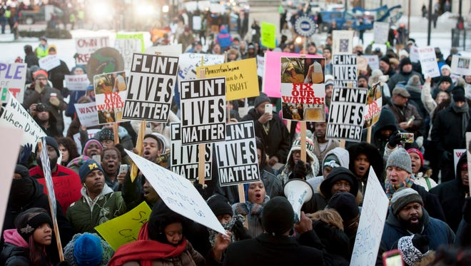 People protest the Flint water crisis outside of the Michigan State Capitol before the State of the State speech, January 19, 2016.