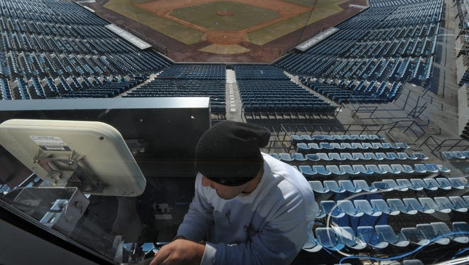 Luis Villegas takes down a Track Man device that measures the speed of pitches as the Nashville Sounds get ready to move to a new stadium.