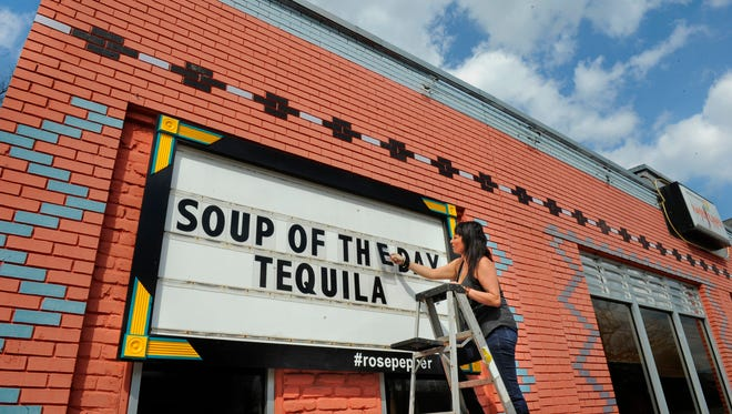 Rosepepper owner Andrea Chaires changes out the marquee in front of the restaurant on Eastland Avenue. The sign has gained notoriety for its clever quips.