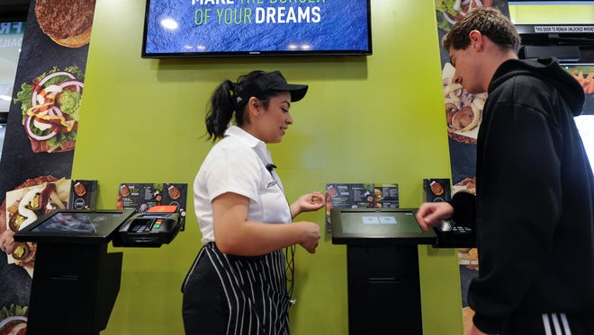 "Amy Sanchez helps customer Michael Slade, 16, order a customized sandwich using a tablet at a McDonald's in Laguna Niguel, Calif. The ""Create Your Taste"" menu program is an experiment being conducted in four Orange County, Calif. McDonald's restaurants."