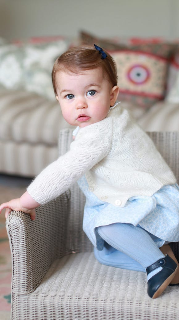 Princess Charlotte, posing in a toddler-sized chair,