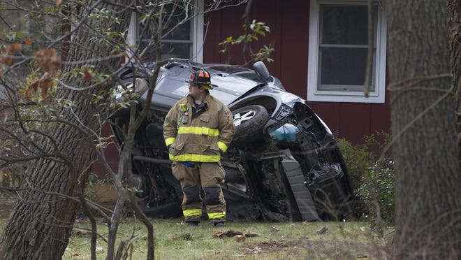 An overturned SUV rests on the lawn of 353 Dover Chester Road.