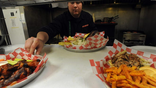 Joey Wilkinson prepares food while working at Mo Jeaux's in Fort Collins in this file photo. The Campus West barbecue bar and grill received a rating of 'excellent' on its most recent public health inspection.