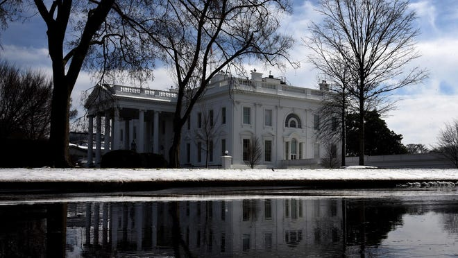 The White House is reflected in a puddle from the melting snow on Feb. 21, 2019, in Washington, D.C.