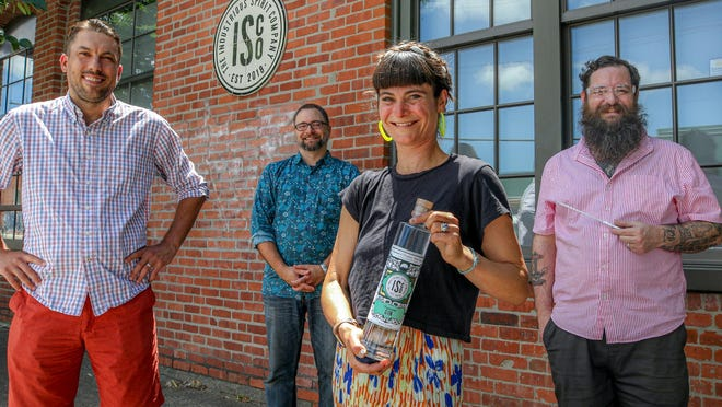 The Industrious Spirit Company is just launching their distilling business in Providence. Co-owner  Manya Rubinstein holds a bottle of their gin,  and is flanked by distiller and creative director Dan Neff (right) and co-owner Doug Randall (left). Tasting room manager Liam Maloney is at back.