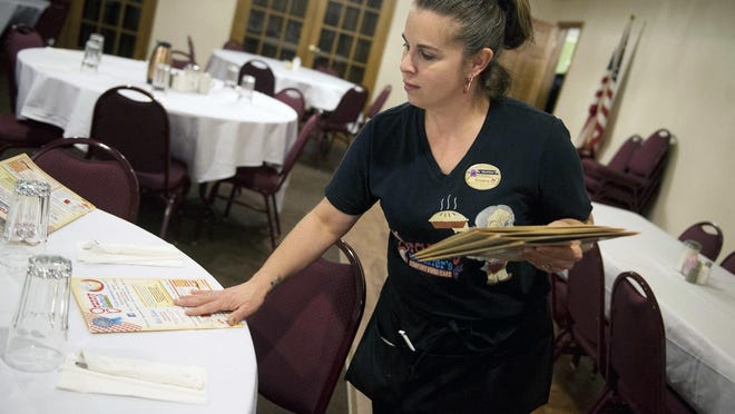 A waitress puts out menus for dinner service. According to the Michigan Department of Labor and Economic Opportunity, the state's scheduled minimum wage increase didn't go into effect as scheduled Friday, Jan. 1 -- affecting many employees in the hospitality and restaurant industries, both of which have been significantly impacted by the ongoing pandemic.