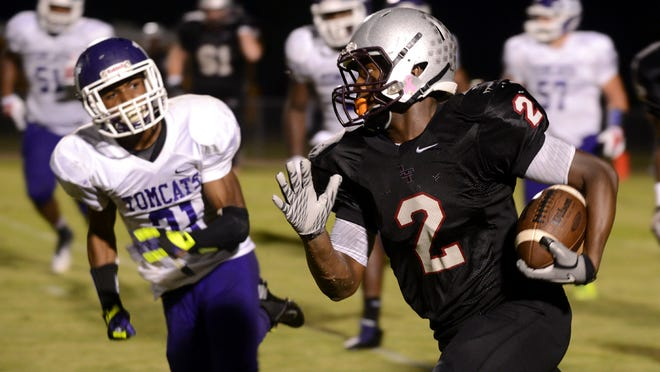 Liberty's Devin Bush runs past Haywood's Markevious Williamson Friday.