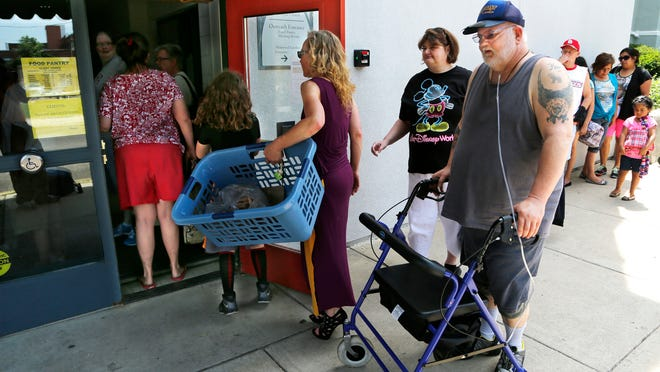 Carl Rohland pushes his walker as he joins other patrons in line for the first St. John's/LUM weekend food pantry Saturday at St. John's Episcopal Church, 600 Ferry Street in Lafayette.