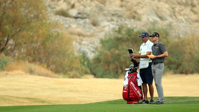 Idyllwild-native Brendan Steele and his caddie talk about the approach shot at the 364-yard par 4 sixteenth hole during the final round of the Humana Challenge on Sunday, January 25, 2015 at the Palmer Private Course at PGA West in La Quinta, Calif. Steele's round of 64 put him in a five-way tie for second at the end of the day.