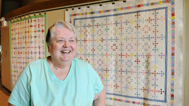 Phyllis Scroggins, facilitator of the quilt display at the Sherburne History Center in Becker, talks about the flour sack or feed sack quilts on display behind her Wednesday.